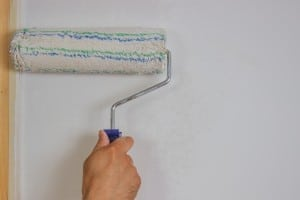 Man hand with roller painting a white wall